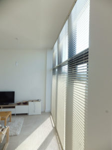 Metal venetian blind in contemporary penthouse living room window.