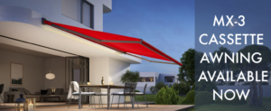 Markilux MX-3 Cassette Awning with red orange fabric extended at night.