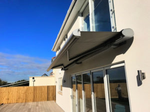Markliux 990 awning beginning to extend over large outdoor decking.