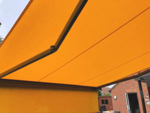Markilux 970 awning with orange fabric fully extended overhead