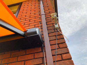 Markilux wind sensor attached to side of orange brick house.