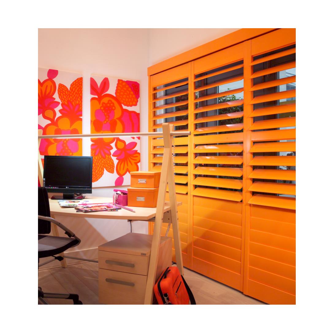 Orange plantation shutters in home office