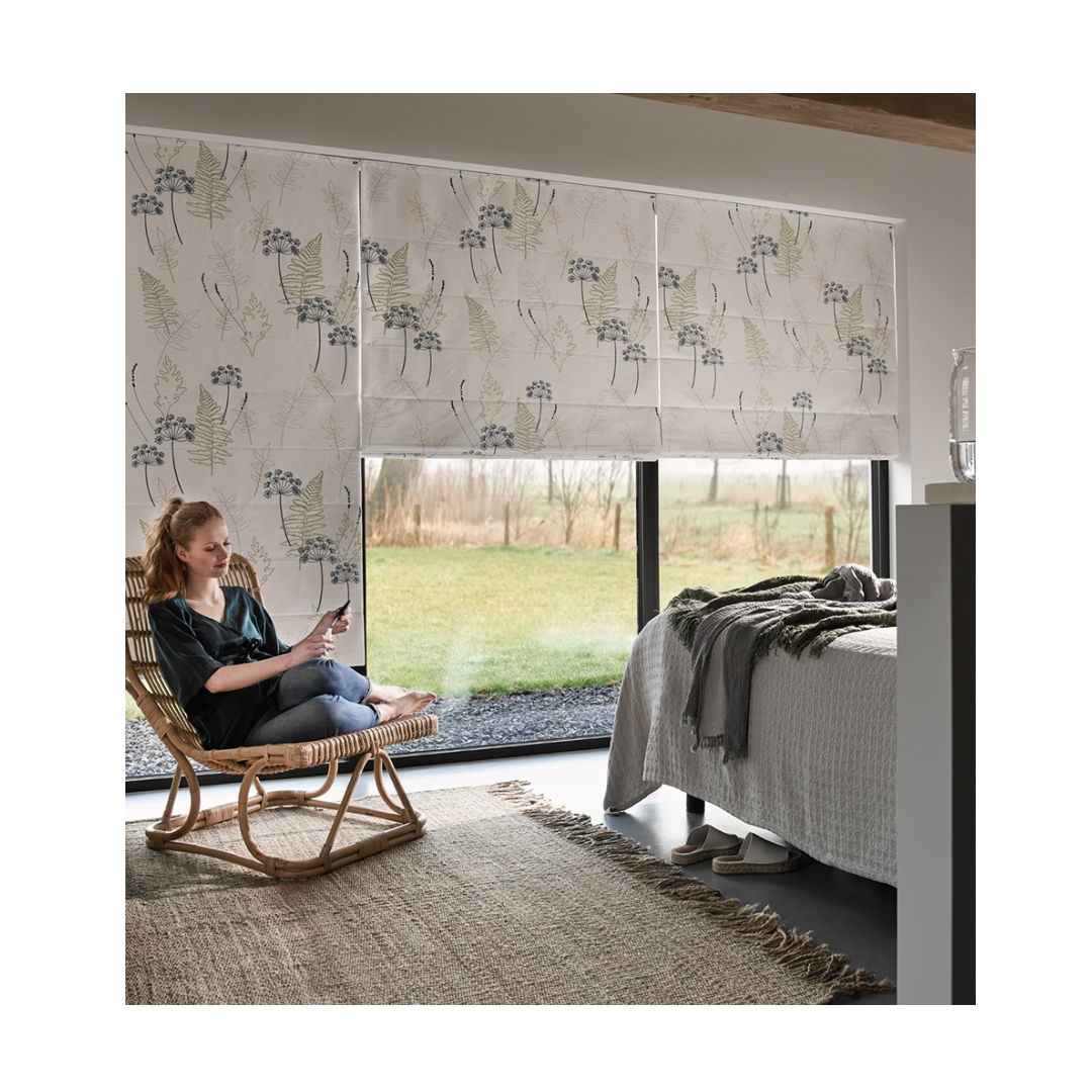Bedroom with roman blinds covering window lady sat relaxing in wicker rocking chair
