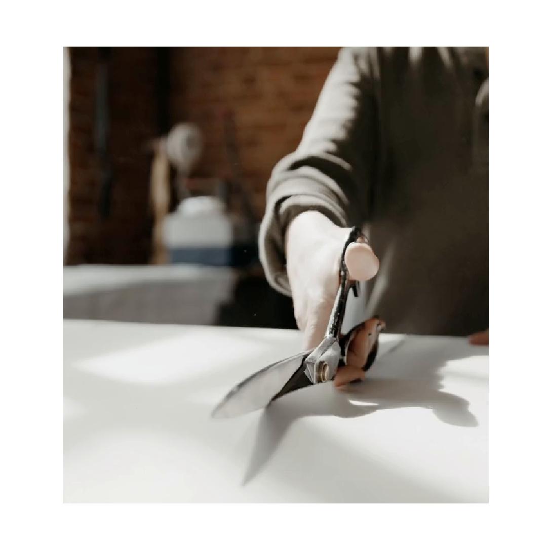 Curtain maker cutting through fabric with scissors